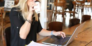 woman in a black shirt drinking coffee while working